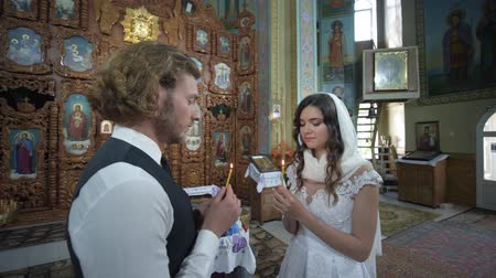 nişanlısı : KHERSON, UKRAINE - JUNE 04, 2019: blessing marriage in church, young fiance and bride with candles in hands stand at temple during wedding ceremony among icon