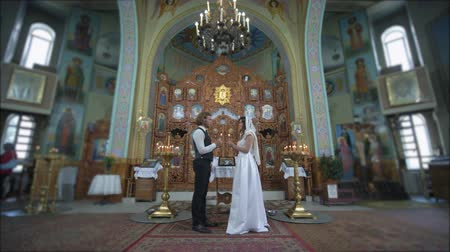 núpcias : KHERSON, UKRAINE - JUNE 04, 2019: marriage ceremony, Loving guy and girl into white wedding dress with candles in hands look into each other eyes during wedding ceremony at church altar with icons Vídeos