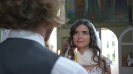 fiancee : KHERSON, UKRAINE - JUNE 04, 2019: Orthodox bridal ceremony, beautiful young bride look into eyes fiance with candles in hands during marriage ceremony at temple close-up