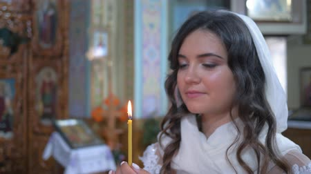 núpcias : KHERSON, UKRAINE - JUNE 04, 2019: Orthodox religion, young woman with faith in eyes holds candle in hands during wedding in church close-up