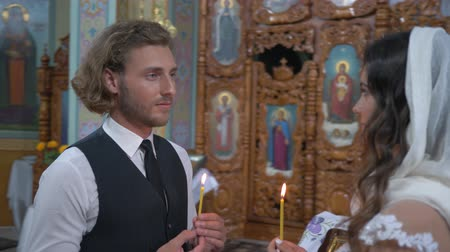 nişanlısı : KHERSON, UKRAINE - JUNE 04, 2019: Orthodox religious traditions, Loving couple newlyweds with candles in hands look into each other eyes during marriage ceremony at temple, close-up