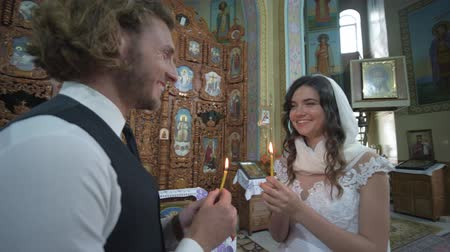 núpcias : KHERSON, UKRAINE - JUNE 04, 2019: wedding church ceremony, happy smiling newlyweds with candles in hands look into each other eyes during marriage ceremony at altar with icons
