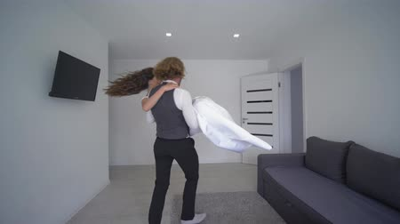 fiancee : happy fiance carries bride on hands in white dress and rotate at new light apartment on wedding day