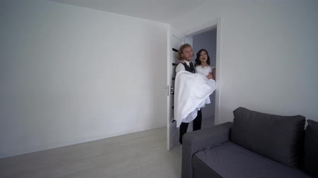 nişanlısı : housewarming, joyful groom carries fiancee on hands in white dress and turns at new light house Stok Video