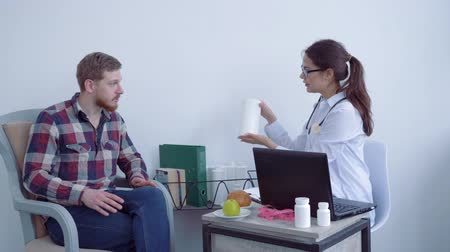 nourishing : medic dietitian girl advises patient guy and recommends dietary supplements healthy for wellness and shows jars of medicament during consultation in bright room Stock Footage