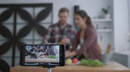 útil : culinary internet vlog, bloggers female and man teach subscribers to cook healthy food from vegetables for weight normalization and wellness while smartphone records live tutorial video in kitchen