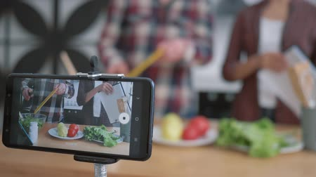 subscribers : diet plan, smartphone makes video recording live how bloggers guy and girl cook healthy eating from fresh vegetables and greens according to diet plan close up on cuisine table Stock Footage
