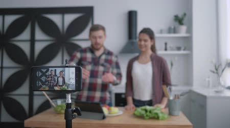 subscribers : health blog, smiling bloggers culinary specialist welcome subscriber and prepare useful food with vegetables and greens in kitchen while camera cell phone records video for followers at social media Stock Footage