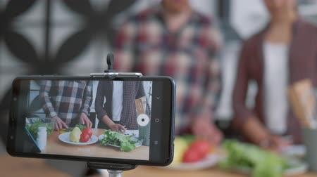 relieves : healthy eating blog, mobile phone makes video recording live how bloggers culinary specialist cook preparing healthy meals from fresh vegetables and greens according to diet plan close up on kitchen Stock Footage