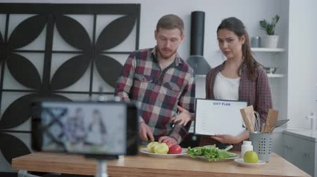 relieves : healthy lifestyle blog, bloggers culinary specialist prepare useful lunch with vegetables and greens in kitchen while camera smartphone records video for subscribers at social networks Stock Footage