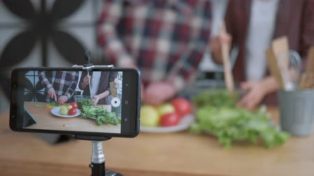 relieves : internet videoblog, smartphone makes video for followers how bloggers man and woman cook preparing healthy meals from fresh vegetables and greens close up on kitchen table Stock Footage
