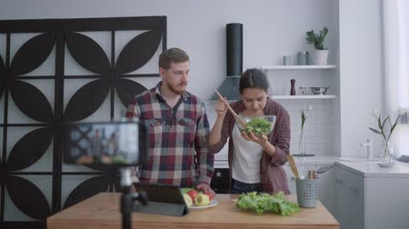 bloggers : nutritional blog, young vloggers man and woman prepare healthy breakfast with vegetables and greens in kitchen while camera smartphone records video for subscribers at social networks
