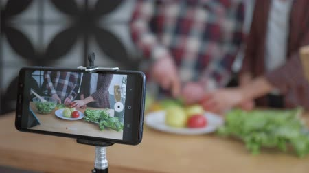 relieves : online blogging, mobile phone makes video for subscribers how bloggers couple cook preparing healthy meals from fresh vegetables and greens close up on kitchen table