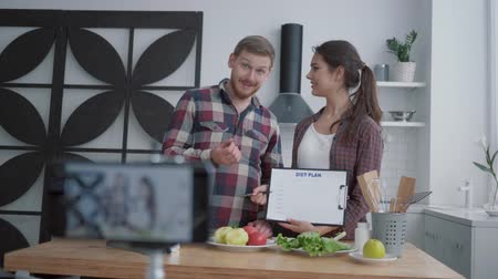 полезный : wellness videoblog, young couple of bloggers broadcast live on healthy nutrition while preparing useful meals from vegetables and greens according to diet plan with dietary supplements at kitchen