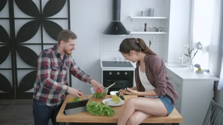 užitečný : crazy family, funny cheerful man is fooling around and making grimaces with vegetables and woman takes picture on smartphone while sitting on table in kitchen while cooking healthy food for lunch