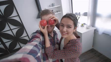 mittagessen : crazy man with woman take selfie video on smartphone and fooling around with vegetables while cooking healthy food on breakfast for wellness according to diet