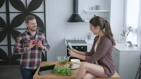 crazy girl : fun cooking, crazy young couple taking selfie photo on cell phone and grimace while cooking healthy vegetable salad for dinner in kitchen Stock Footage
