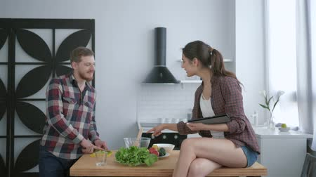 užitečný : healthy food, young man prepares useful vegetarian eating on lunch and woman sitting on kitchen table with tablet in hands and and advice to cooking at cuisine Dostupné videozáznamy
