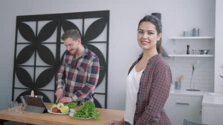 nourishing : portrait of happy female on kitchen, smiling woman looks at male who prepares healthy useful meal from vegetables for breakfast using tablet on cuisine table at home Stock Footage