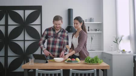 nourishing : portrait of young family in kitchen, happy husband and wife prepares food for breakfast with fresh vegetables on cuisine table using tablet with video lesson