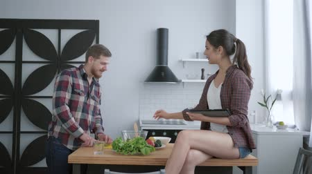 полезный : vegetable nutrition diet, bearded man prepares delicious healthy salad from fresh vegetables and greens and woman sits on table with tablet in hand and talks in kitchen Стоковые видеозаписи