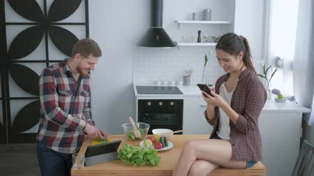 полезный : weight normalization, man prepares healthy vegetarian salad on breakfast and woman sitting on kitchen table with smartphone in hands and takes selfie photo at cuisine