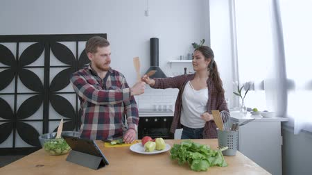 полезный : young funny woman with man dancing and having fun while cooking healthy eating from vegetables on lunch for wellness according to diet plan on cuisine table Стоковые видеозаписи