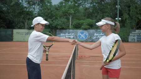 contestant : KHERSON, UKRAINE - JUNE 09, 2019: Start of tennis match, girl and boy tennis players meeting by net and greeting each other shaking hands before tournament on court and walking on positions Stock Footage