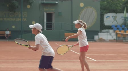 contestant : KHERSON, UKRAINE - JUNE 09, 2019: tennis training, sports couple of tennis players boy and girl teenagers practising serve technique at workout before match on court outdoors