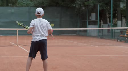 дух : KHERSON, UKRAINE - JUNE 09, 2019: professional sports, ambitious boy playing tennis with rivals and hitting racket on ball pass through net to each other at court during game under rain