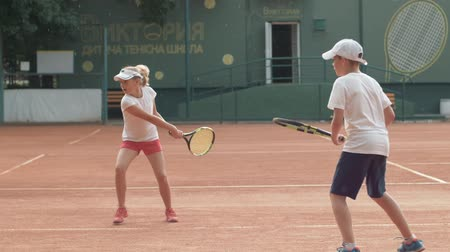 contestant : KHERSON, UKRAINE - JUNE 09, 2019: tennis school, purposeful sports child boy and girl learn to play tennis and hitting racket on ball at red court on open air under rain