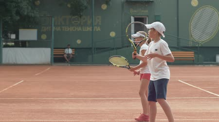 野心的な : KHERSON, UKRAINE - JUNE 09, 2019: tennis training, sports ambitious teenager boy and girl playing tennis and hitting racket on ball at red court outdoors under rain