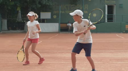 contestant : KHERSON, UKRAINE - JUNE 09, 2019: tennis workout, active determined teens boy and girl playing tennis and hitting racket on ball at red court on open air under rain