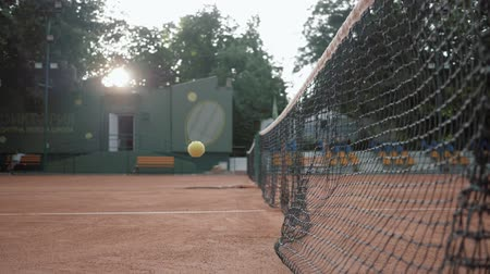 outdoor hobby : KHERSON, UKRAINE - JUNE 09, 2019: Yellow tennis ball hit net and bounces back on red court close up in slow motion on open air
