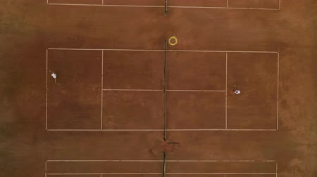 eye ball : aerial survey of tennis court, ambitious sports players guy and girl play tennis on red court and pass ball to each other through net on match