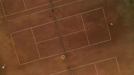 eye ball : aerial view of tennis game, ambitious sports players boy and girl play tennis on red court and pass ball to each other through net on match