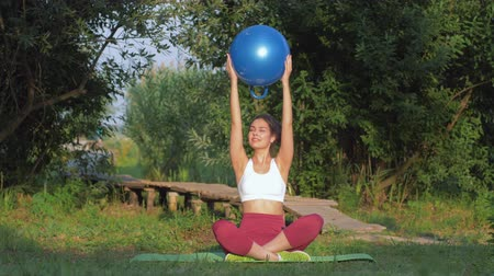 wooden bridge : fitness outdoors, young woman doing exercises for arm muscles with large fitness ball sitting on mat on green lawn in open air