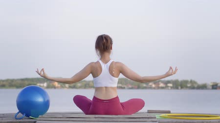 meditál : healthy lifestyle, young attractive yogi girl in lotus position meditates and delight spiritual calmnes on nature near river
