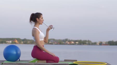 закалки : healthy lifestyle, young smiling athletic female drinks mineral clear beverage from bottle while doing sports and enjoy rest in nature on river against sky Стоковые видеозаписи