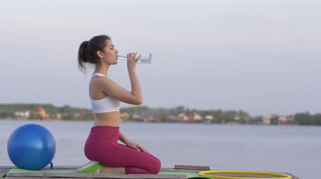 закалки : quenching thirst, young happy sports girl drinks mineral clear water from bottle while doing fitness and enjoy rest in nature on river against sky