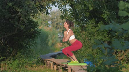 construção muscular : sports activities, amazing girl performing sports squat exercise during workout in open air on wooden bridge among green vegetation