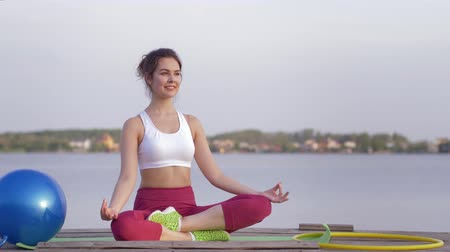 meditál : yoga lifestyle, beautiful yogi woman in lotus position meditates and relish spiritual calmnes outdoors near water