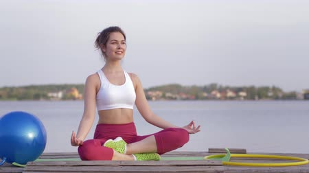 meditál : yoga relaxing, young attractive yogi girl in lotus position meditates and delight spiritual calmnes on nature near river
