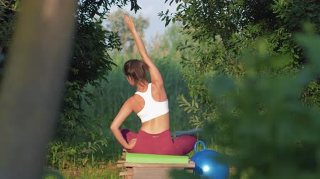 chakra : Yoga sport, fitness girl in lotus position doing exercises with body tilts to sides sitting on wooden bridge in nature among green trees and grass Stock Footage