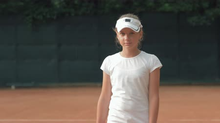 ambition : portrait of ambitious tennis player girl with racket into hands on red court on open air close-up