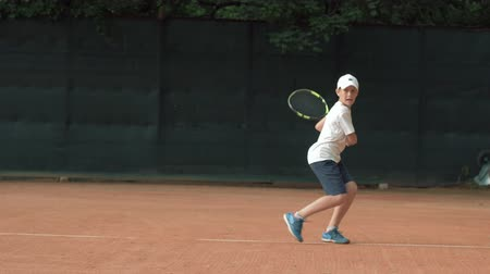 competidores : Tennis game, ambitious tennis player adolescent boy concentrating and focusing on game and racket hit ball on red court in open air Archivo de Video