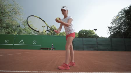 честолюбивый : concentrated and serious tennis player teen girl hitting racket on ball at professional red court during championship outdoors, Slow motion Стоковые видеозаписи