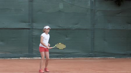 служить : professional sport, tennis player adolescent girl concentrating and focusing on game then hitting racket on ball at professional red court