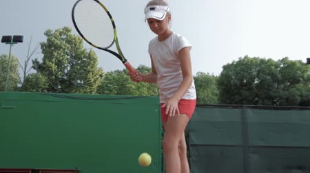 contestant : sport lifestyle, professional athlete child girl plays at sports game and hitting racket on ball at professional red court during competition on open air Stock Footage