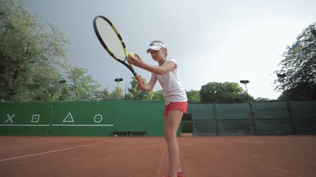 честолюбивый : tennis game, ambitious sport player adolescent girl hitting racket on ball at professional red court during tournament on open air, Slow motion
